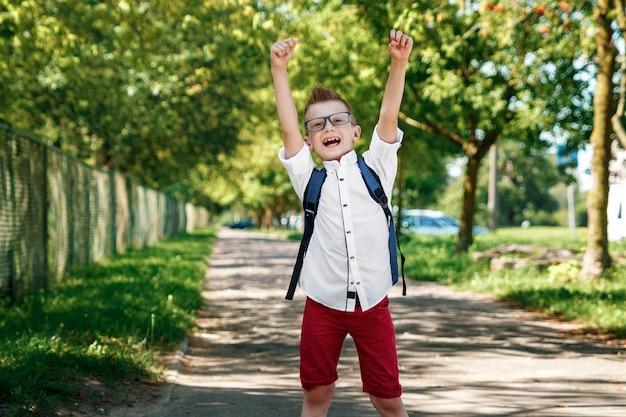 路上でバックパックを持った小学校の少年 Premium写真