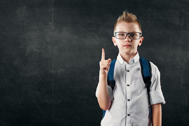 Портрет мальчика из начальной школы на фоне школьной доски Premium Фотографии