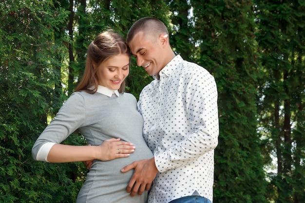 幸せな妊娠中の女性、公園で家族カップル Premium写真