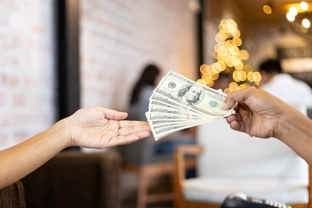 Человеческие руки обменивают долларовые деньги Premium Фотографии
