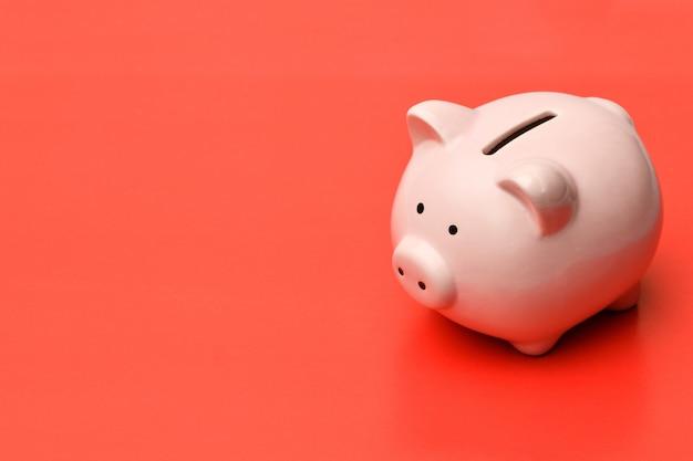ピンクの貯金箱は、影付きの赤い背景の右側に立っています。 Premium写真
