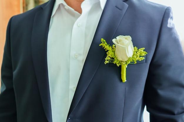 新郎の男の胴体の断片の青いジャケットと白いバラのブートニアと白いシャツ Premium写真
