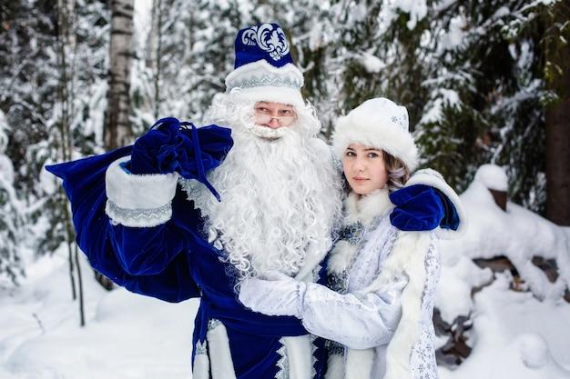雪に覆われた森の中のロシアのクリスマスキャラクター、デド・モロス(父フロスト)とスネグーラチカ(雪の乙女)。 Premium写真