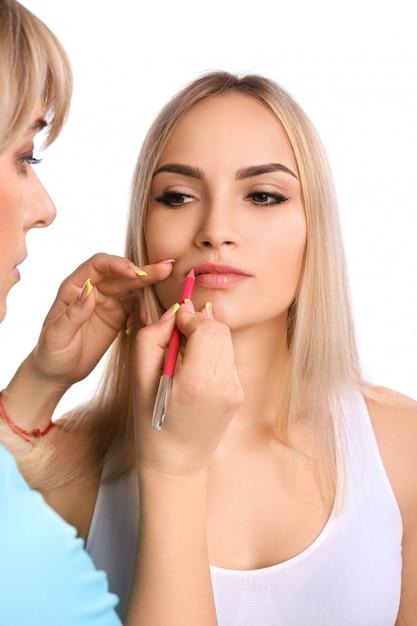 Косметолог делает перманентный макияж на губах женщины Premium Фотографии