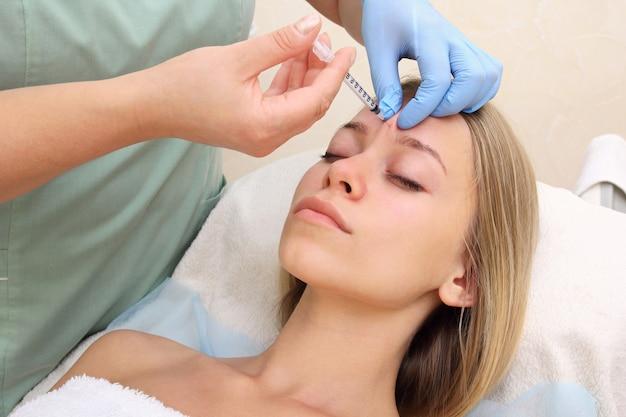 Красивая женщина получает укол в лицо. Premium Фотографии