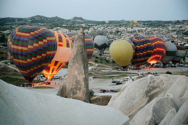 トルコのカッパドキアギョレメ国立公園に着陸する熱気球。 Premium写真