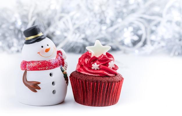 Счастливого рождества с красным кексом и снеговиком Premium Фотографии