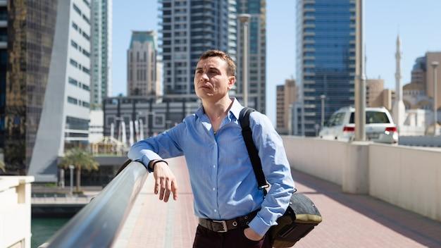 35歳の40歳の男性が大都会の中心に立ち、興味を持って周りを見回しています。 Premium写真