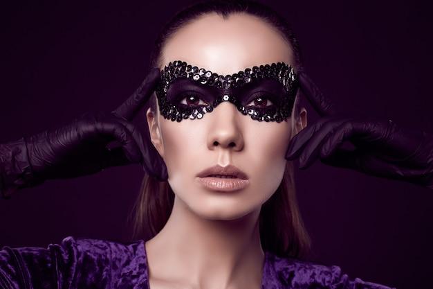 Очаровательная элегантная брюнетка в маске с блестками и перчатках Бесплатные Фотографии