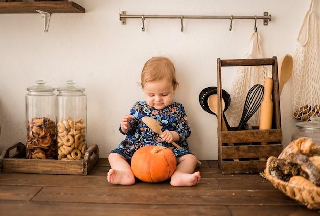 Девочка в голубом платье сидит на деревянной кухне Premium Фотографии