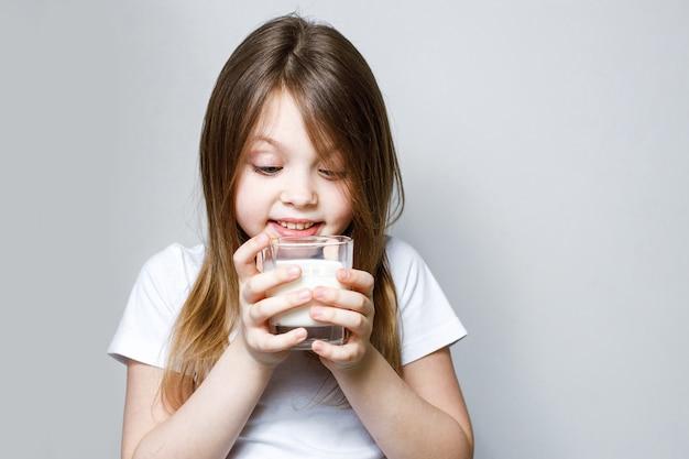 Девочка радостно смотрит на стакан молока Premium Фотографии