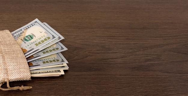 Мешок с деньгами на темном деревянном фоне. копировать пространство Premium Фотографии
