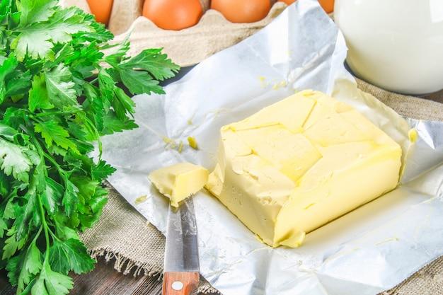 バターの棒はミルク、卵、パセリに囲まれて、ナイフで木の板の上にばらばらに切られます Premium写真