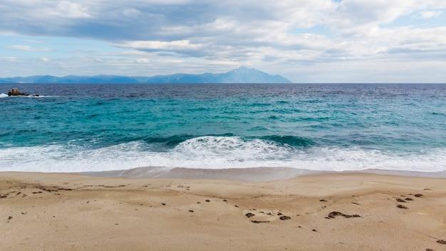 Пляж с голубыми волнами эгейского моря и горы Бесплатные Фотографии