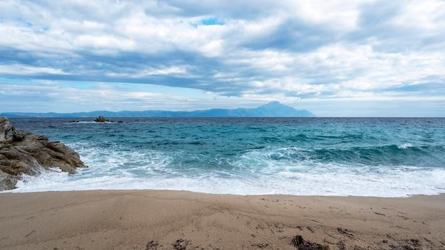 Пляж со скалами и голубыми волнами эгейского моря, суши и гор. Бесплатные Фотографии