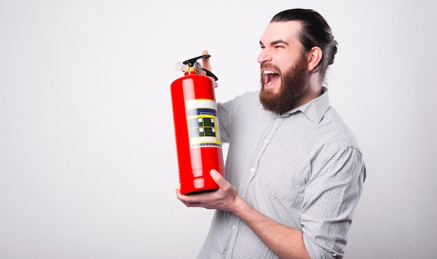 Бородатый мужчина кричит с огнетушителем в руках, глядя в сторону возле белой стены Premium Фотографии