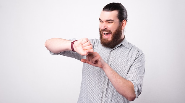 あごひげを生やした若い男は、彼が白い壁の近くで遅れていることを恐れて彼の時計にストレスを感じている Premium写真