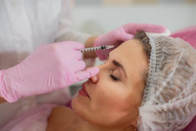 Косметолог вводит ботокс в лицевые мышцы лба своего пациента. Premium Фотографии