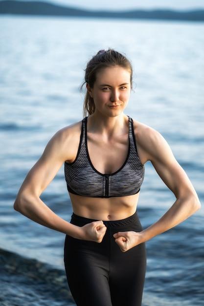 아름답고 펌핑 된 여성은 여름 저녁에 호수 기슭에 서있는 동안 팔에 펌핑 된 근육을 보여줍니다. 프리미엄 사진