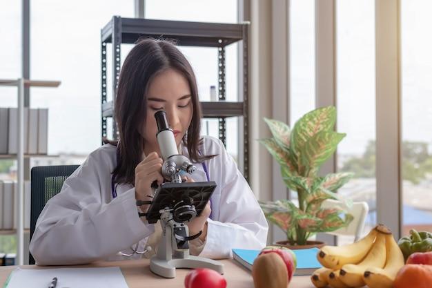 아름 다운 아시아 여성 의사는 큰 유리 창 배경으로 현대 사무실 책상에서 현미경을 살펴 봅니다. 프리미엄 사진