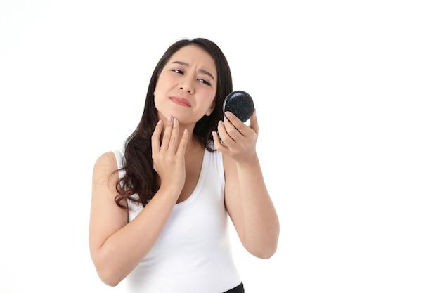 美しいアジアの女性はストレスを感じています。彼女は彼女の頬ににきびを見て、鏡を持っています。美容コンセプト、白い背景 Premium写真