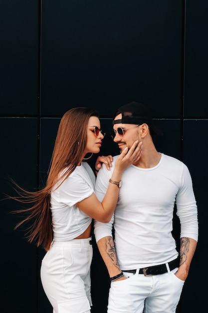 白いスタイリッシュな服を着た美しいカップルが街を歩いています。 Premium写真