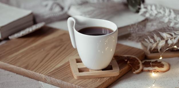 나무 스탠드에 차 또는 커피와 함께 아름다운 컵. 가정의 편안함 개념. 무료 사진