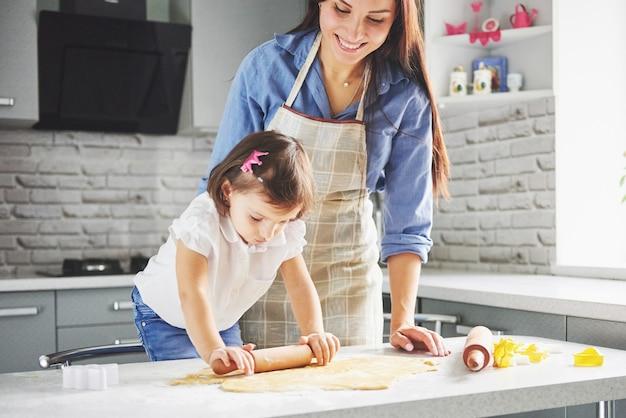 台所で料理をしている母親と一緒に美しい娘 無料写真
