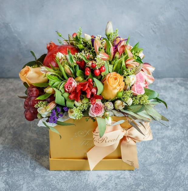 Красивый букет цветов с гранатом и виноградом в желтой коробке с бабочкой Бесплатные Фотографии