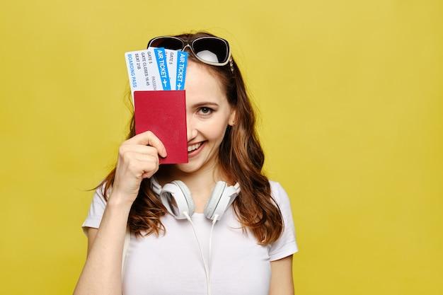 カジュアルな服装の美しい少女は、顔の半分をカバーするパスポートと航空券を持っています。 Premium写真