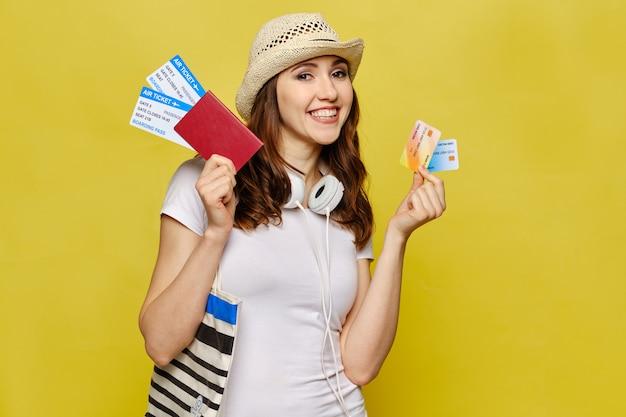 カジュアルな服装の美しい少女は、クレジットカードでパスポートと航空券を持っています。 Premium写真