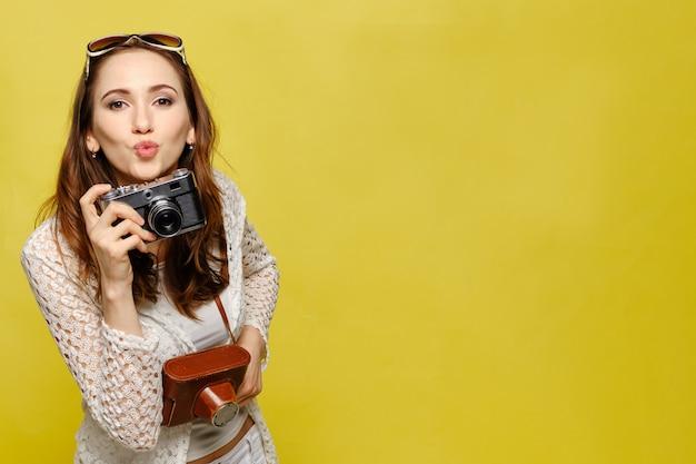 ビンテージカメラでカジュアルな服装の美しい少女がカメラを見てキスを送ります。 Premium写真