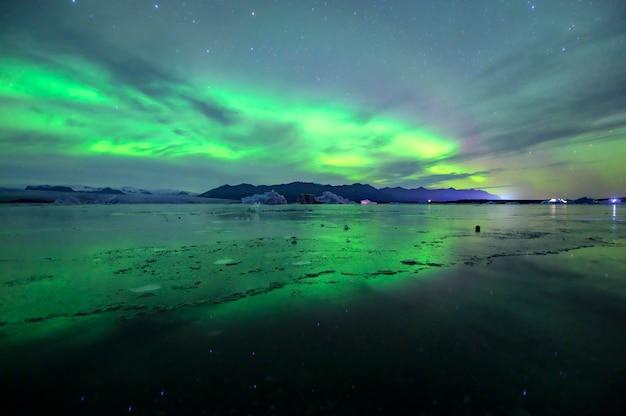 아이슬란드의 Jokulsarlon 라군에서 아름다운 녹색과 빨강 오로라 춤 프리미엄 사진