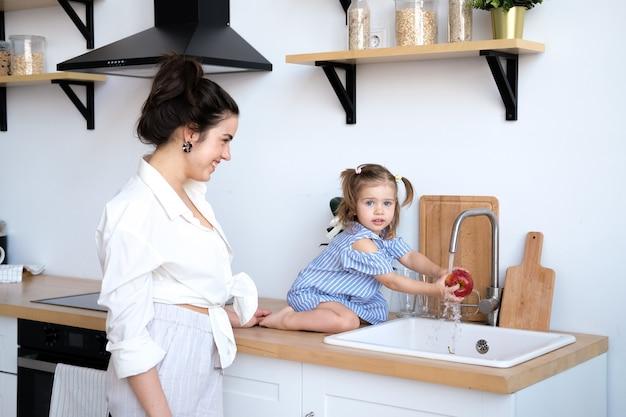 彼女の2歳の娘を持つ美しい母親は台所の流しで果物を洗っています Premium写真