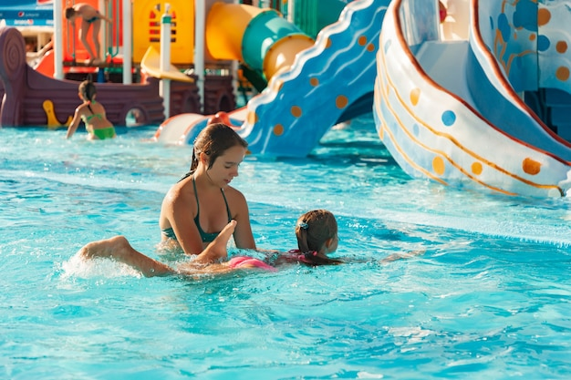 아름다운 언니가 여동생이 맑고 투명한 물로 수영장에서 수영하는 법을 배우도록 도와줍니다. 프리미엄 사진