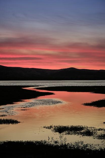 Красивый летний закат на берегу озера с разноцветным небом и отражениями в воде. длительное воздействие Premium Фотографии