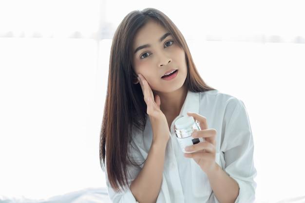 Красивая азиатка, использующая средства по уходу за кожей, увлажняющий крем или лосьон, ухаживающий за ее сухой кожей. увлажняющий крем в женских руках. Premium Фотографии
