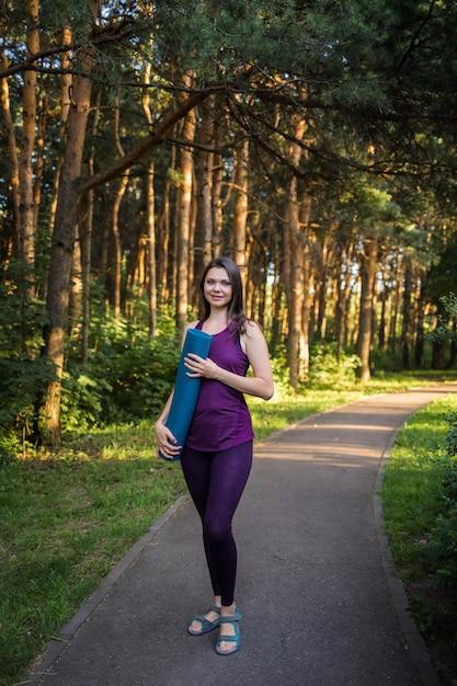 Красивая женщина-спортсменка в форме с матом для тренировок стоит на дорожке в парке Premium Фотографии