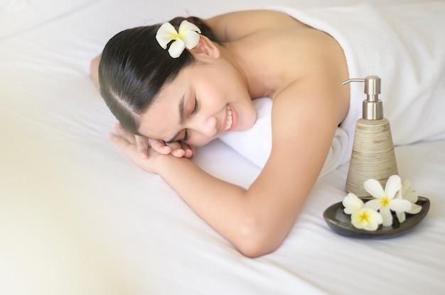 美しい女性はリラックスしてスパリゾート、マッサージ、美容トリートメントのコンセプトでマッサージをしています。 Premium写真