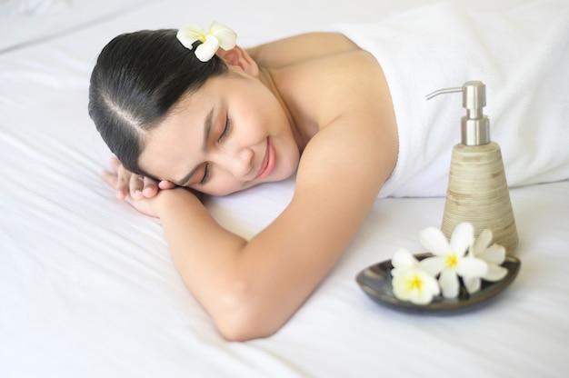 Красивая женщина расслабляется и делает массаж на спа-курорте, концепция массажа и косметических процедур. Premium Фотографии