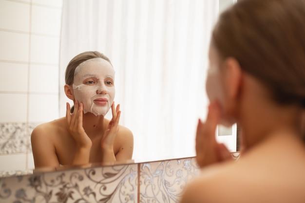 아름다운 여인이 부드럽게 얼굴을 거울로 욕실의 화장품 마스크를 넣습니다. 프리미엄 사진