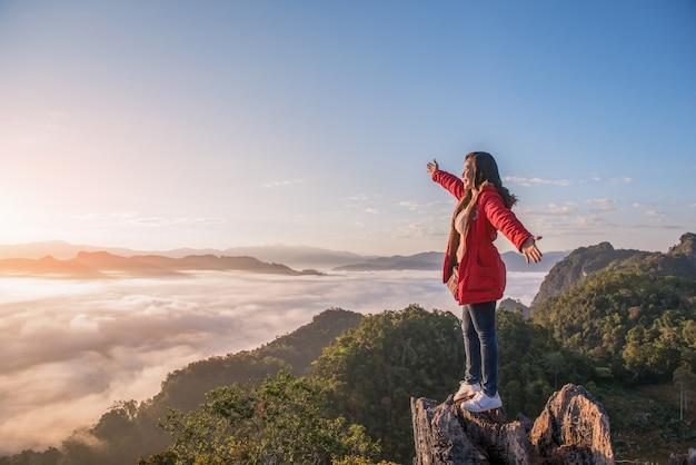 Красивая женщина, стоящая на горе в пху пха мок бан джабо в провинции мае хонг сон, таиланд. Premium Фотографии