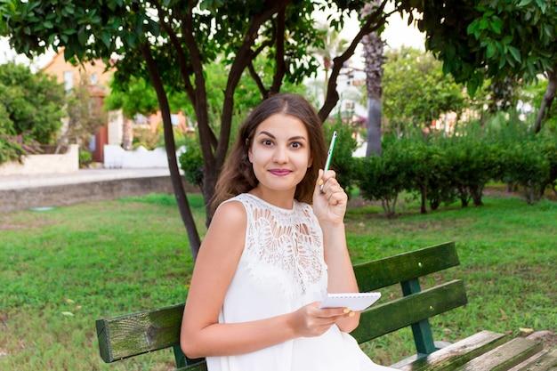 Красивая женщина, которая держит блокнот и ручку, Premium Фотографии