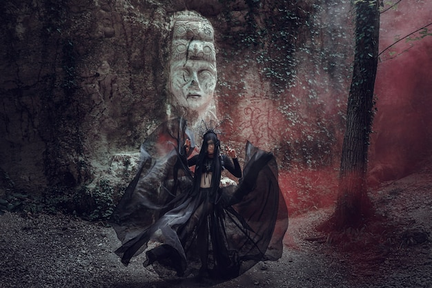 黒のドレスと黒の王冠の薄い肌の美しい女性。ゴシックルック。ハロウィーンの衣装。偶像の彫刻に対して有色煙を持った女性 Premium写真