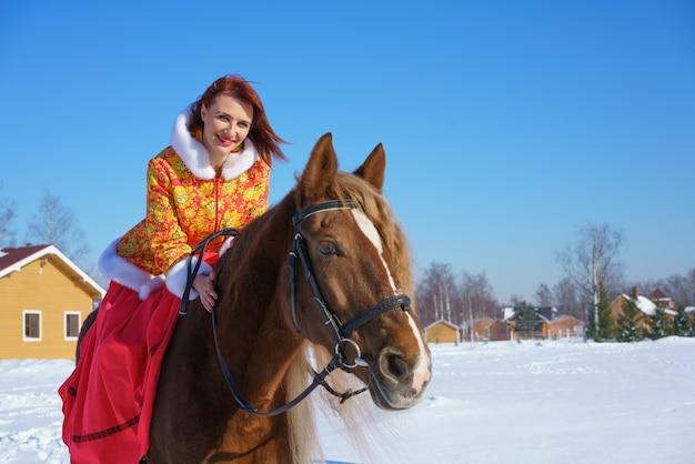 따뜻한 노란색-빨간색 재킷을 입은 아름다운 어린 소녀가 겨울 맑은 서리가 내린 날에 말을 탄다. 겨울철에 승마 스포츠에 종사 무료 사진
