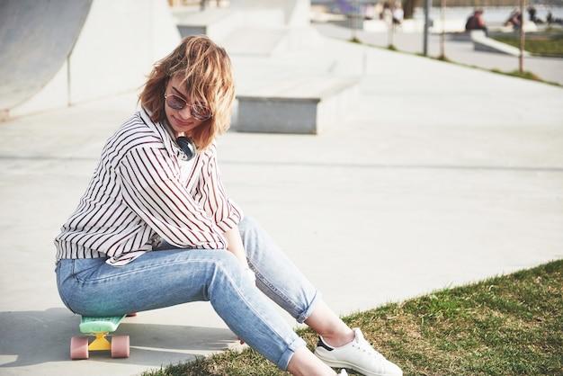 Красивая молодая девушка развлекается в парке и катается на скейтборде. Бесплатные Фотографии
