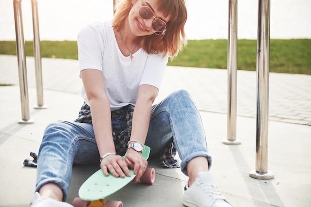 美しい少女が公園で楽しんでいて、スケートボードに乗っています。 無料写真