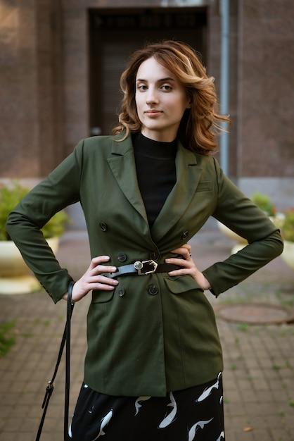 昼間に通りでカメラにポーズをとって髪と化粧品でスタイリッシュな服の美しい若い女性。 Premium写真