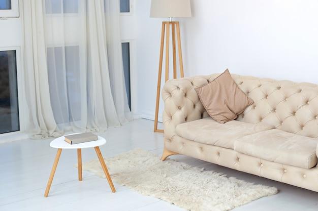 Бежевый диван с декоративной подушкой, журнальным столиком и лампой в просторной белой гостиной. просторный интерьер комнаты с удобным диваном возле большого окна. концепция комфорта. домашний декор Premium Фотографии