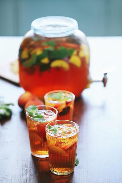 Большая банка и три стакана персикового сока Бесплатные Фотографии